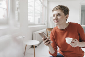 Smiling woman with cell phone and espresso cup - KNSF03278