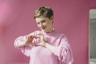 Portrait of woman in pink twinkling shaping heart with her hands - KNSF03296