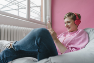 Smiling woman in beanbag with cell phone and headphones - KNSF03302