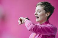 Woman in pink sportswear wearing smartwatch - KNSF03317