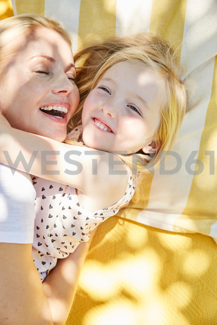 Happy girl and mother hugging on a blanket - SRYF00598 - Martina Ferrari/Westend61