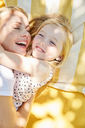 Happy girl and mother hugging on a blanket - SRYF00598