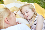 Smiling girl and mother lying on a blanket - SRYF00601