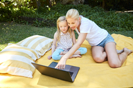 Girl and mother using laptop on a blanket - SRYF00607