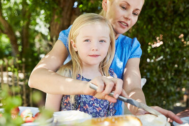Girl with mother having breakfast at garden table - SRYF00613