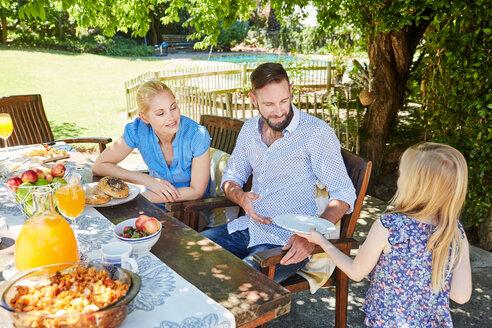 Girl serving plates for family at garden table - SRYF00619