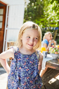 Portrait of smiling girl with mother in the background at garden table - SRYF00622