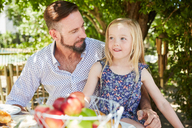 Girl with father sitting at garden table - SRYF00625