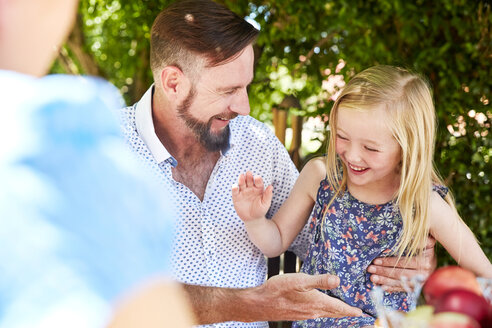 Happy girl with father sitting at garden table high fiving - SRYF00628