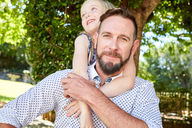 Portrait of smiling father carrying daughter piggyback - SRYF00640