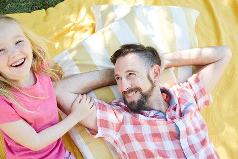 Happy girl with father lying on a blanket - SRYF00646