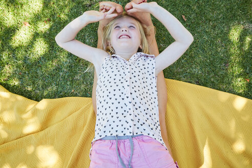 Happy girl lying on a blanket playing with mother's feet - SRYF00655