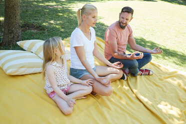 Family with girl practicing yoga on a blanket - SRYF00658