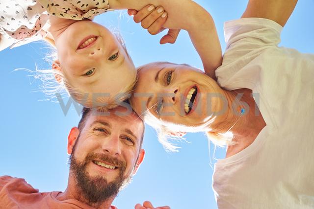 Portrait of happy family huddling under blue sky - SRYF00673