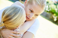 Daughter and mother hugging outdoors - SRYF00676