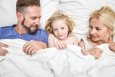 Portrait of smiling family lying in bed - SRYF00691