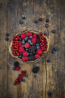 Wickerbasket of various berries on wood - LVF06563