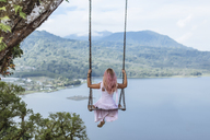 Indonesia, Bali, young woman sitting on swing - KNTF00935