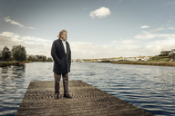 Senior man standing on jetty at a lake - KNSF03326