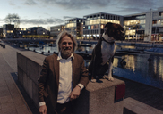 Portrait of smiling senior man with dog at the lakeside in the evening - KNSF03329