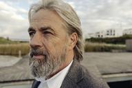 Portrait of serious senior man at lakeshore - KNSF03338
