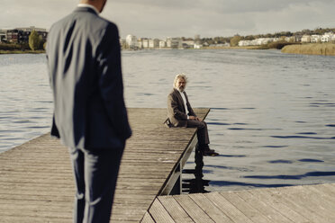 Senior man sitting on jetty at a lake with man in foreground - KNSF03341