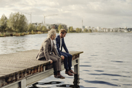 Two businessmen sitting on jetty at a lake - KNSF03344