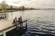 Two businessmen sitting on jetty at a lake talking - KNSF03347