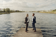 Two businessmen standing on jetty at a lake talking - KNSF03350