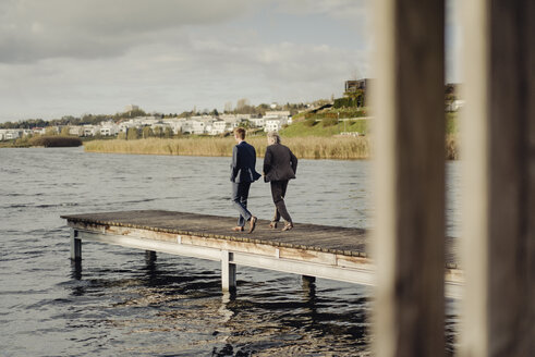Two businessmen walking on jetty at a lake - KNSF03353