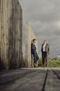 Two businessmen standing on boardwalk talking - KNSF03356