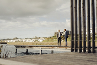 Two businessmen standing on jetty at a lake talking - KNSF03362