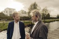 Two businessmen talking at a lake - KNSF03365