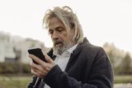 Serious senior man holding cell phone outdoors - KNSF03374