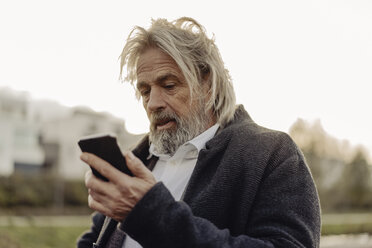 Serious senior man holding cell phone outdoors - KNSF03374