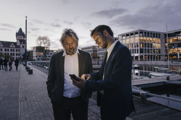 Two businessmen with cell phone at city harbor at dusk - KNSF03377
