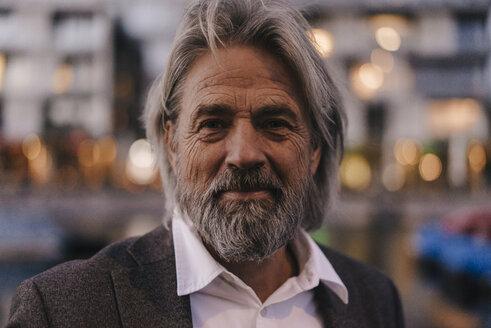 Portrait of confident senior man outdoors at dusk - KNSF03380
