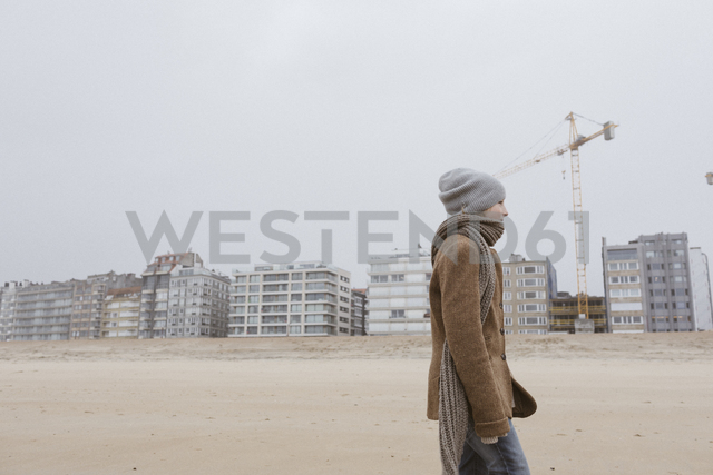Germany, North Sea Coast, boy strolling on the beach in winter - KMKF00101