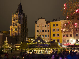 Germany, Cologne, view to historic town hall and row of houses with Christmas market in the foreground - WIF03477