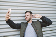 Portrait of smiling man taking selfie with smartphone showing victory sign - RAEF01956