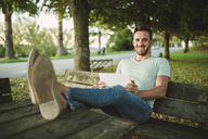 Portrait of relaxed man using tablet outdoors - RAEF01962