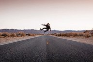 USA, California, Joshua Tree, young man jumping on a road - WVF00861