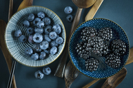 Wooden spoons, bowl of blueberries and bowl of blackberries on blue ground - ASF06141