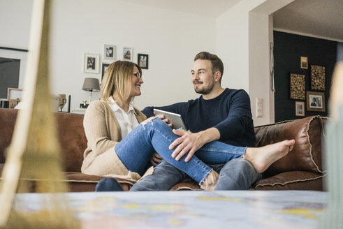 Smiling couple sitting on couch at home with tablet - MOEF00583