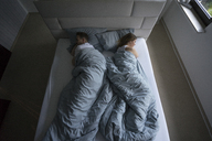 Top view of couple lying in bed at home - MOEF00613