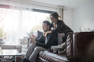 Smiling couple sittng on couch at home using tablet - MOEF00622