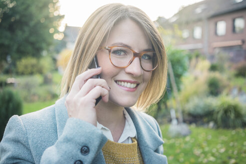 Portrait of smiling woman on cell phone in garden - MOEF00628