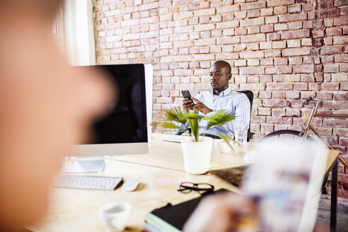 Businessman using cell phone in office with colleague in foreground - HAPF02591