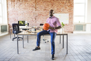 Happy businessman with basketball at desk in office - HAPF02621