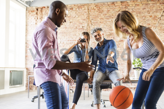 Woman taking picture of colleagues playing basketball in office - HAPF02627